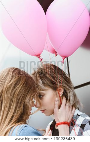Young Lesbian Couple Kissing And Holding Air Balloons Outdoors
