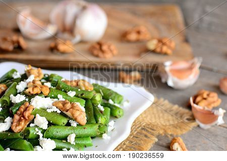 Healthy green beans salad with balsamic dressing. Warm green bean salad with cottage cheese, walnuts, garlic and spices on a plate and an old wooden table. Side dish or veggie main dish