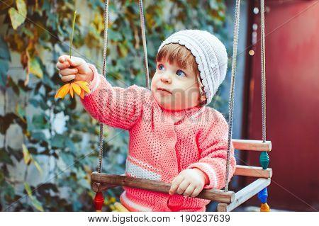 Girl swinging on a swing in the garden