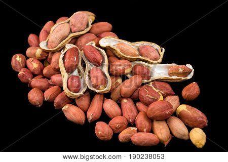 Peanuts in nutshell and peeled peanuts on black background