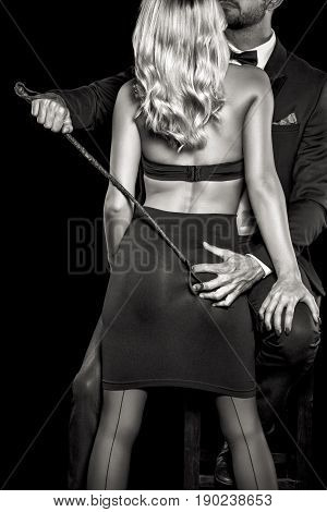 Man in tux with whip grab woman lover ass by hand black and white isolated