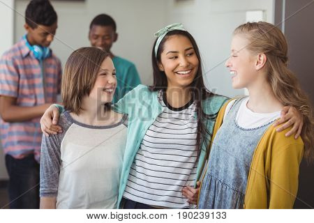 Smiling schoolgirls standing with arms around in corridor at school