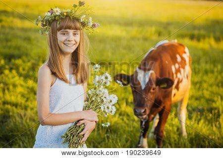 Joyful Little Girl On A Sunset Meadow With A Calf