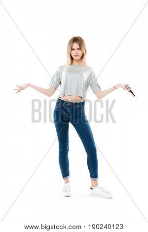 Displeased woman wearing t-shirt and jeans with smartphone looking camera isolated over white