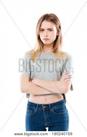 Portrait of an angry disappointed girl standing with arms folded and looking at camera isolated over white background