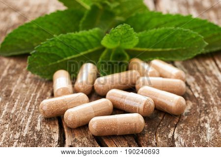 Natural medicine in capsules leaning on an old wooden table against the background of green leaves