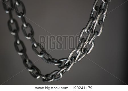Metal chain hanging on a gray background. As in a dungeon.