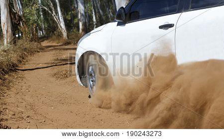 Rally Car turning in dirt track, dust splash