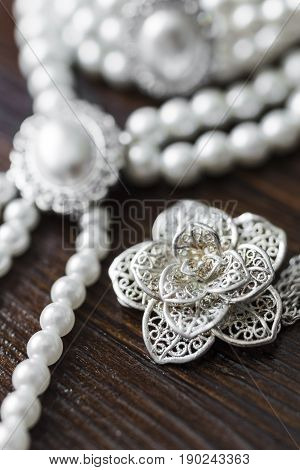 A bracelet and a necklace of white pearls and a large pearl surrounded by diamonds and a silver brooch in the form of a flower lie on a dark brown wooden background.