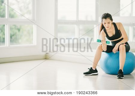 Sexy Asian girl exercising with dumbbell on fitness ball at fitness gym with copy space sport and healthy lifestyle concept