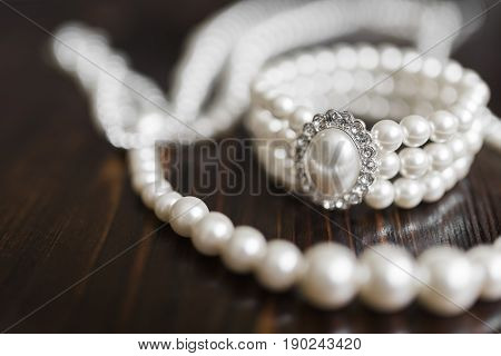A bracelet made of white pearls with a large pearl surrounded by diamonds and a pearl necklace lie on a dark brown wooden background.