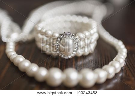A bracelet made of white pearls with a large pearl and diamonds and a pearl necklace lie on a dark wooden background