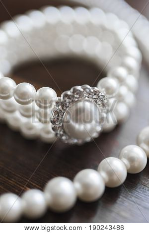 Pearl bracelet with a large white pearl and diamonds on a dark wooden background