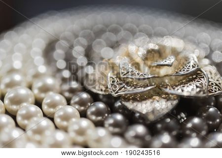 A large silver brooch in the form of a flower lies on a necklace of black and white pearls