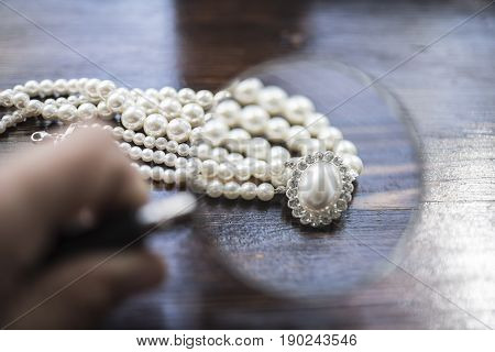 A necklace of white pearls with a large pearl surrounded by diamonds lies on a dark brown wooden background