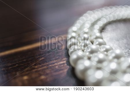 A pearl necklace of white pearls lies on a dark brown background on the right side of the frame.