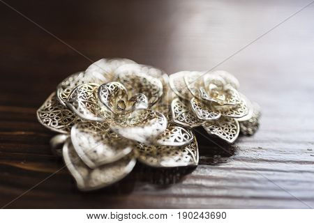 Large and small silver brooches in the form of a flower lie on a dark brown wooden background