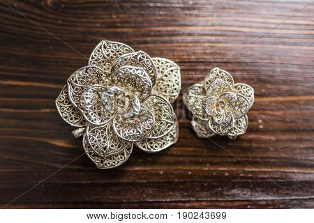 Large and small silver brooches in the form of a flower lie on a dark brown wooden background top view.