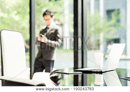 Laptop computer digital tablet and coffee on executive or manager table in modern office. Asian businessman or entrepreneur using smartphone in background. Business communication technology concept