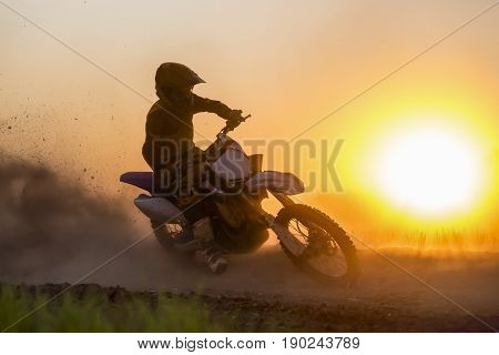 silhouette of motocross rider jumping in track.