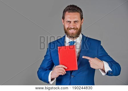 man or happy businessman pointing on notebook red book in hand in blue outfit on grey background copy space business saving book