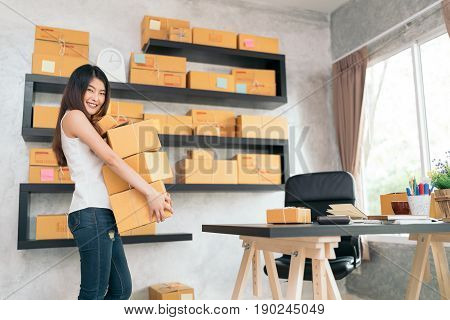 Young Asian small business owner carrying product boxes at home office online marketing packaging and delivery scene startup SME entrepreneur or freelance woman working at home concept