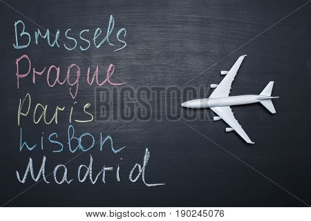 Traveling concept. Toy plane over chalkboard with cities written on it