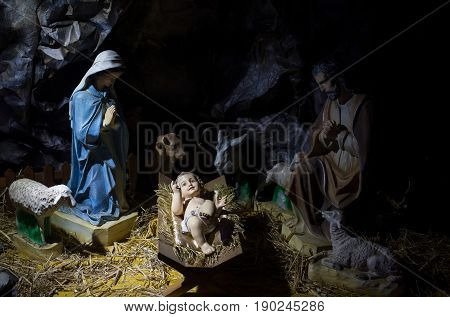 Nativity scene. Child Jesus lying in manger or crib in cave or barn. Figurines of virgin Mary saint Joseph sheep donkey ox. Christianity religion. Holy family. Christmas holidays celebration