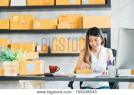 Young Asian small business owner working at home office taking note on purchase orders. Online marketing packaging delivery startup SME entrepreneur or freelance woman concept