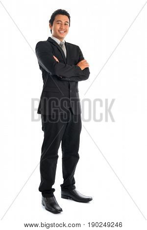 Full body attractive young Southeast Asian businessman arms folded standing isolated on white background. Asian malay male model.