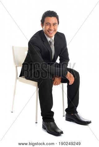 Full body attractive young Southeast Asian businessman sitting on chair, isolated on white background. Asian malay male model.