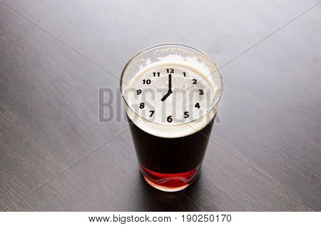 Clock silhouette on foam in beer glass on black table, view from above.