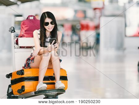 Young Asian girl using smartphone waiting for flight at airport sitting on baggage trolley or luggage cart. Mobile communication technology or travel abroad concept with copy space