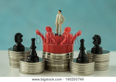 Miniature figure business man standing on red crown king with stack of coins and chess symbol as financial business growth success concept.