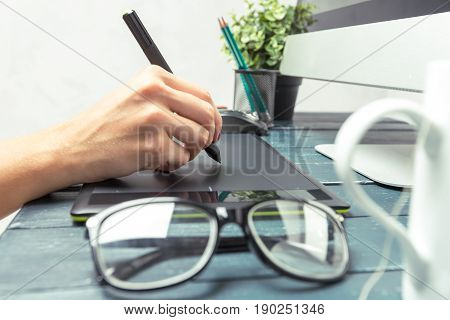 Hand of graphic designer working with stylus and tablet