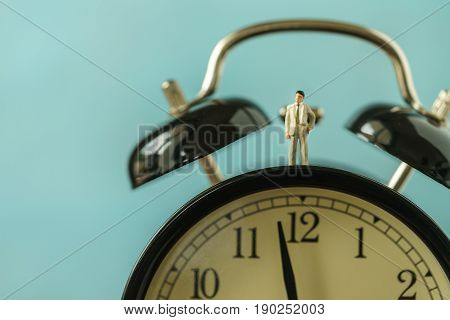 Miniature businessman figure standing on alarm clock as business or time countdown concept.