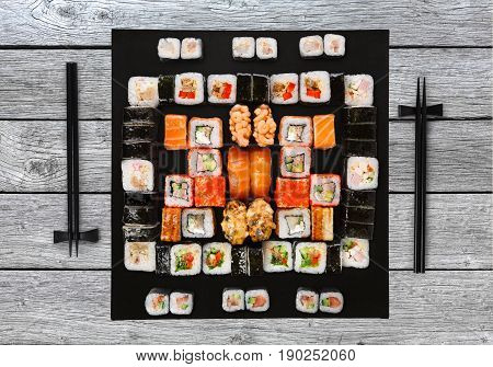 Japanese food restaurant delivery - sushi maki, unagi, gunkan and roll big party platter set on blue wood background, above view