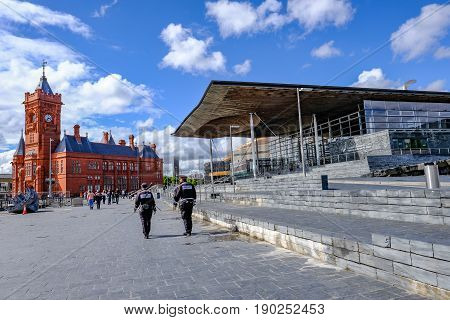 Cardiff Bay Cardiff Wales - May 20 2017: Sinedd National Assembly building and Pierhead builidng. Welsh Government buildings with Community Police officers walking on the path in front.
