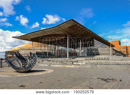 Cardiff Bay Cardiff Wales - May 20 2017: Sinedd National Assembly building. Front view with sculpture in the foreground.