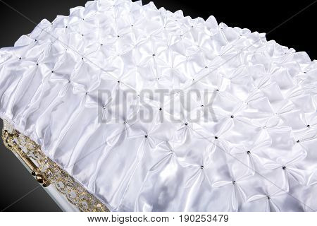closed wooden white coffin covered with white ritual blanket isolated close-up. Ritual object for burial. Surrender body dust of the earth. Christian funeral ritual