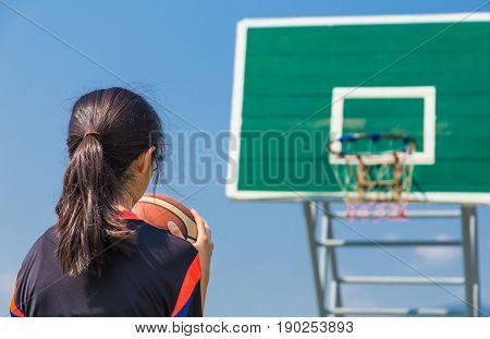 female teenager getting ready to shoot a free throw basketball at an outdoor basketball court on a bright sunny day