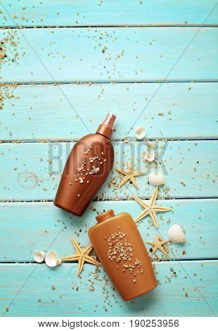 suntan cream bottle on wooden board, seashells