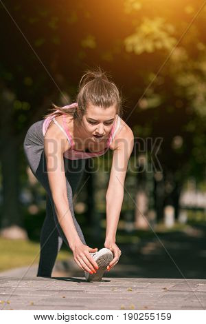 Fit fitness woman doing stretching exercises outdoors at park. Girl doing hamstring leg stretching exercise and stretches. Female sports model exercising outdoor in summer.