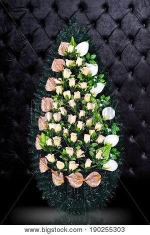 Luxury Funeral wreath with flowers isolated on royal dark background. Ritual object for funeral