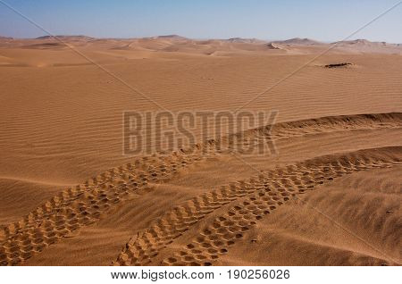 Paired sets of dune buggy tracks in the Kalahari Desert crossing the photo from lower left to upper right; scalloped dunes and sky in background