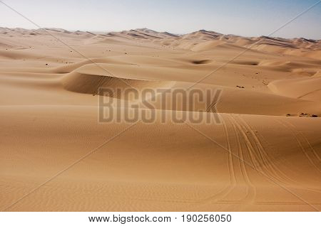 Wind-blown dune on thirds-line in middle of Kalahari desert; additional wind-swept dune buggy tire marks in right foreground; scalloped dunes and sky in distant background