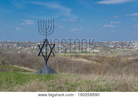 The menorah is a symbol of Judaism the national-religious sign of Israel. The six-pointed star of David. Monument to the victims of the Holocaust in the village of Bogdanovka. Ukraine.