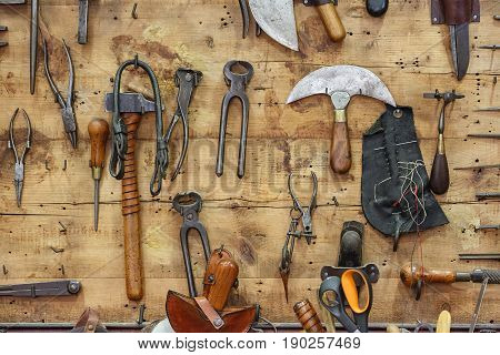The tools of a tanner hanging on the wooden wall in a tannery.