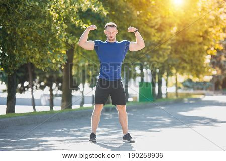 Fit fitness man doing exercises outdoors at park. The man doing exercises. The male sports model jumping outdoor in summer.