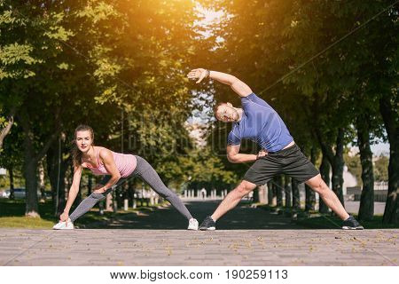 Fit fitness woman and man doing stretching exercises outdoors at park. Couple doing hamstring leg stretching exercise and stretches. Female amd male sports models exercising outdoor in summer. poster